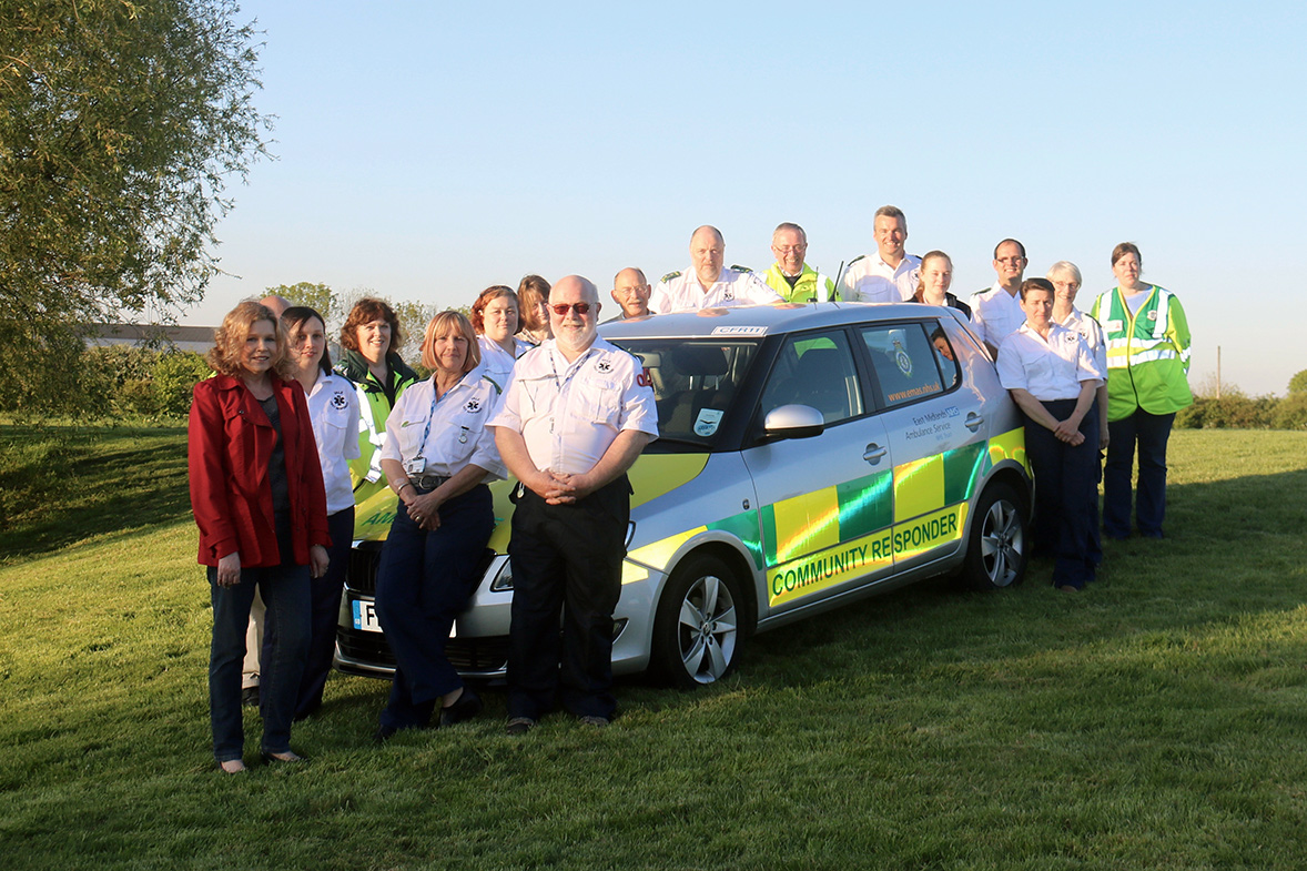 The Vale Responders team stood around a community responder car, taken from above with a drone