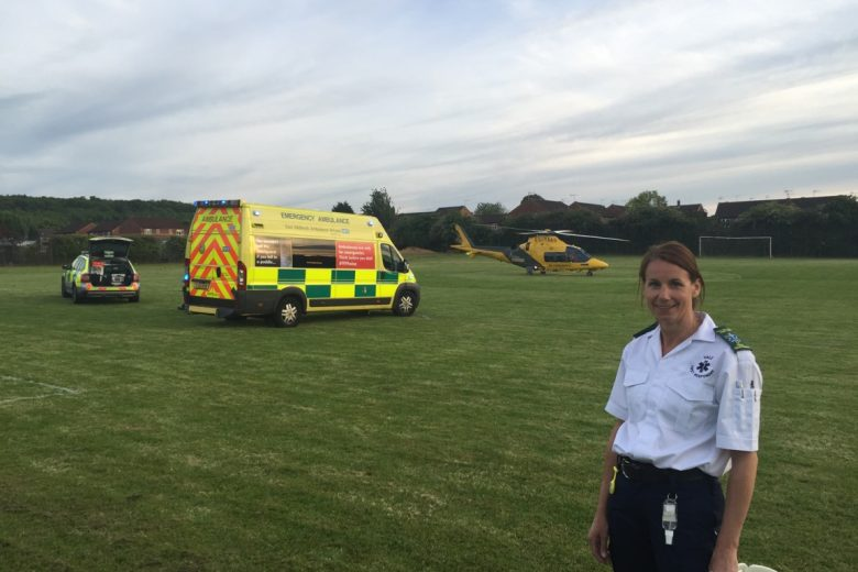 A member of Vale Responders stood in a field with a paramedic car, an ambulance and an air ambulance
